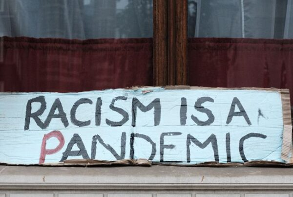 Banner that reads 'racism is a pandemic'